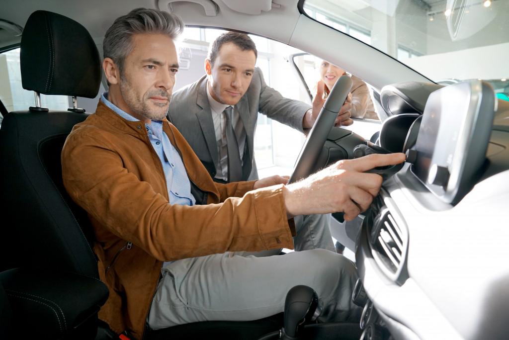 Car salesman showing car features to client