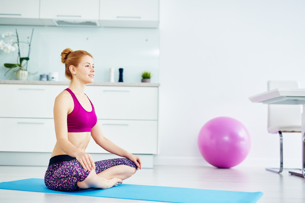 woman doing yoga exercises at home on floor
