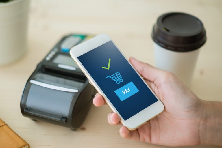 hand holding a cellphone and making transaction online